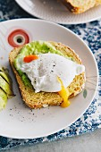Oat and sweet potato bread topped with avocado and a poached egg
