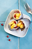 Rollmops (pickled herring fillets) with mango and pomegranate seeds
