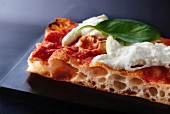 A slice of tomato, burrata and basil pizza