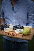 A man holding a cheese board with grapes, pear and almonds