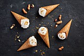 Banana and coconut ice cream in cones next to peanuts