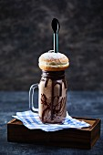 A chocolate freak shake with a doughnut on the top