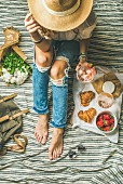 A woman wearing ripped jeans holding a glass of wine next to strawberries and croissants on a picnic blanket