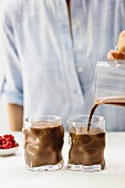 A woman pouring chocolate smoothie out of a jug into glasses