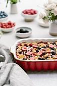 Bread Pudding mit Beeren und Ziegenkäse in Auflaufform auf Tisch