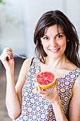 Woman eating a grapefruit