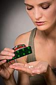 Woman taking Baclofen tablets