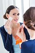 Woman using blotting paper on oily skin