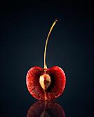 Red cherry in half against black background