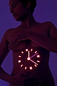 Woman with clock projected on stomach