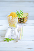 A pineapple ice cream sundae with a stemmed glass