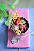 A muesli ice cream sundae with raspberries and oats