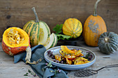 Roasted pumpkin wedges in front of different types of pumpkins