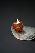 A chocolate truffle decorated with gold leaf