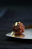 A dark truffle praline decorated with gold leaf