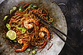 Udon stir-fry noodles with shrimp in wok pan on dark stone background