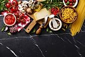 Verschiedene italienische Lebensmittel auf schwarzem Marmoruntergrund