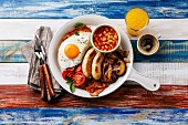 English breakfast in white pan with fried eggs, sausages, bacon, beans, toast, orange fresh and coffee on wooden background