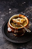Authentic French Onion soup with dried bread and cheddar cheese in bowl on dark background