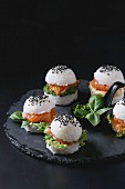 Mini rice sushi burgers with smoked salmon, green salad and sauces, black sesame served on slate stone board