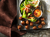 Meatballs with lettuce and a chilli dip