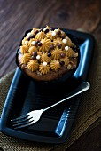 A salted caramel cupcake on a black plate with a fork