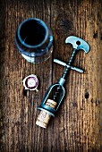 An antique corkscrew with a cork, and a glass of red wine on a wooden surface
