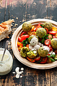 Wild garlic and spinach falafel on a bed of colourful vegetables