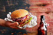 A beefburger with red onions and salad