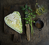 A halved pointed cabbage with loveage, rapeseed oil and caraway