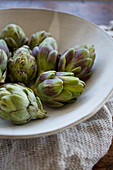 Artichokes in a beige bowl with a beige towel underneath