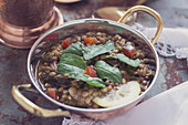 Lentil spinach curry in a copper pan