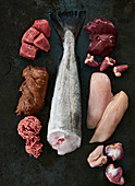 Meat, fish, offal and chicken breast on a black background (ingredients for dog food)