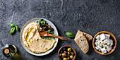 Hummus serviert mit Oliven, Brot und Feta (Aufsicht)
