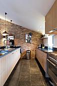 Küchenzeile und lange Theke in umgebauter Scheuen mit Backsteinwand in umgebauter Scheune
