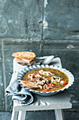 Mediterranean fish soup with tomatoes and bread