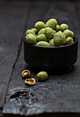 Wasabi peanuts in a black bowl