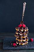 Gestapelte Waffeln mit Schokoladensauce und Himbeeren