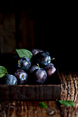 Fresh plums in a square-shaped bowl on a wooden background