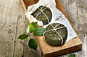 Two pecorino cheeses with stinging nettle rind on a wooden board
