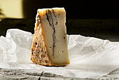 A wedge of pecorino with truffle on white paper