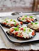 Portobello mushroom pizzas with cheese and tomato