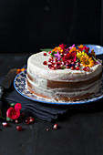 A 'naked cake' with edible flowers and pomegranate seeds