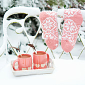 Two cups of hot chocolate on a snow-covered garden bench
