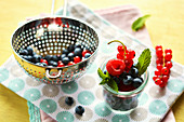 Fresh summer fruits in a glass and metal sieve