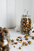 Loose hazelnuts on a table and in a glass storage jar