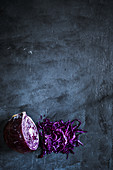 Red cabbage halved and shredded on a dark grey surface