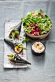 Nori rolls on savoy cabbage salad with watercress and pomegranate seeds