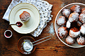 Doughnuts with icing sugar on an étagère and a plate with spoon of jam