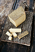 Cheese with a wild flower rind on a wooden chopping board